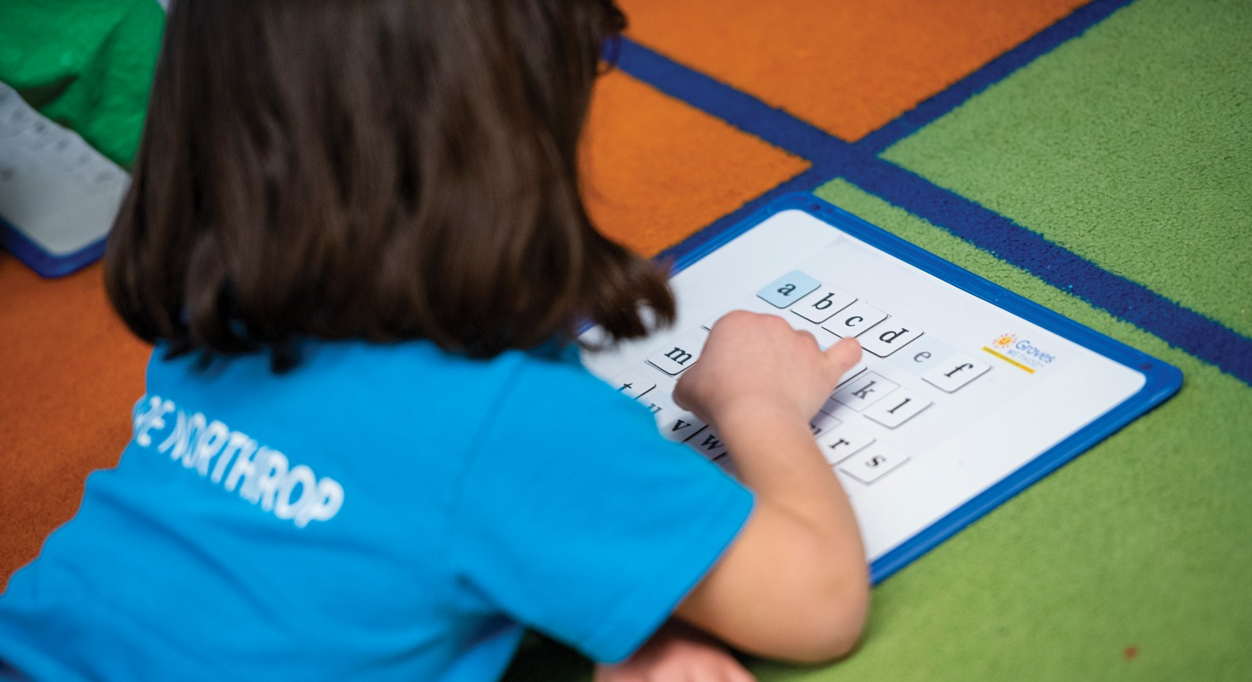 young girl student moving letters on a magnet board