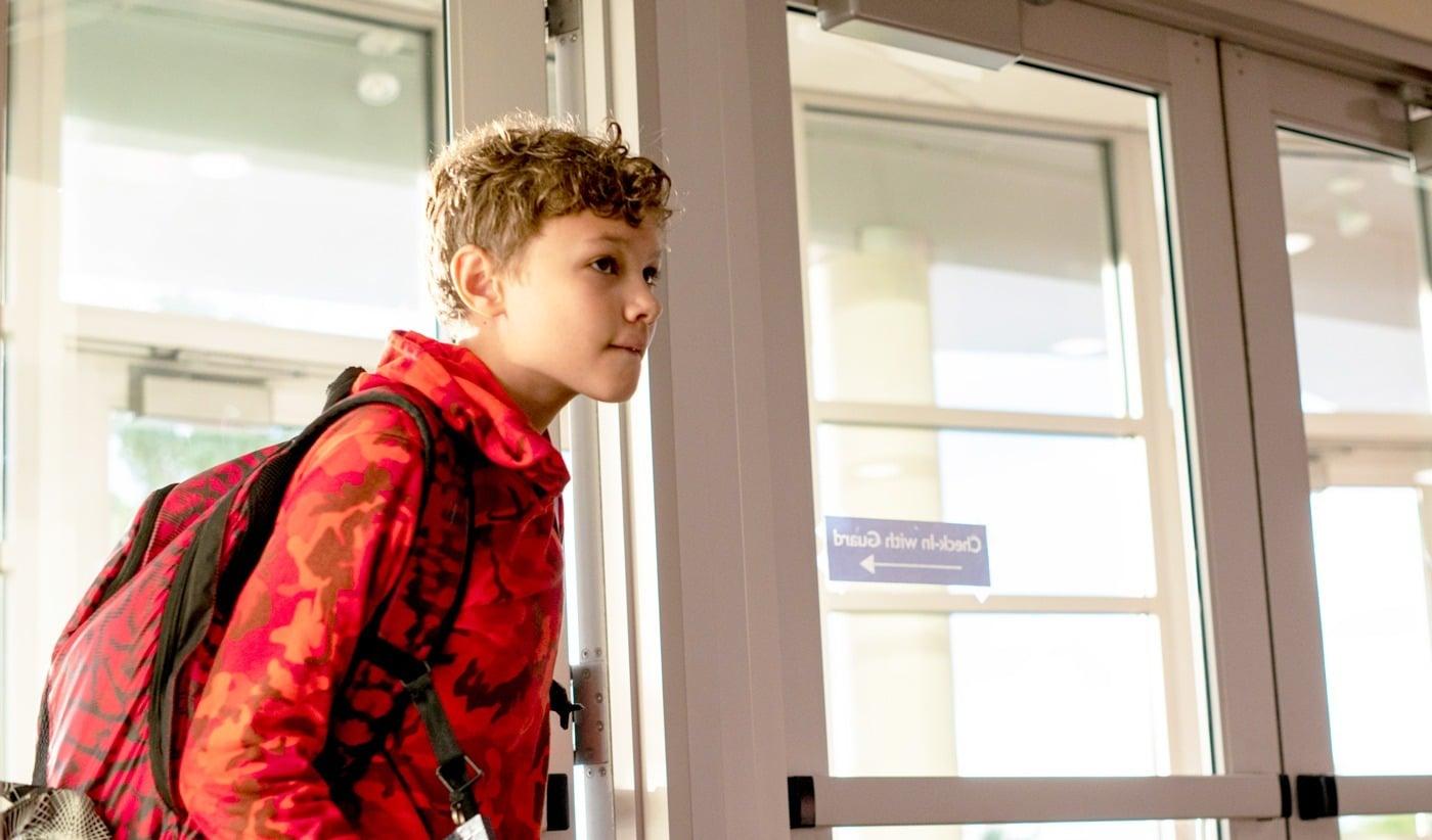 boy student walking through doorway