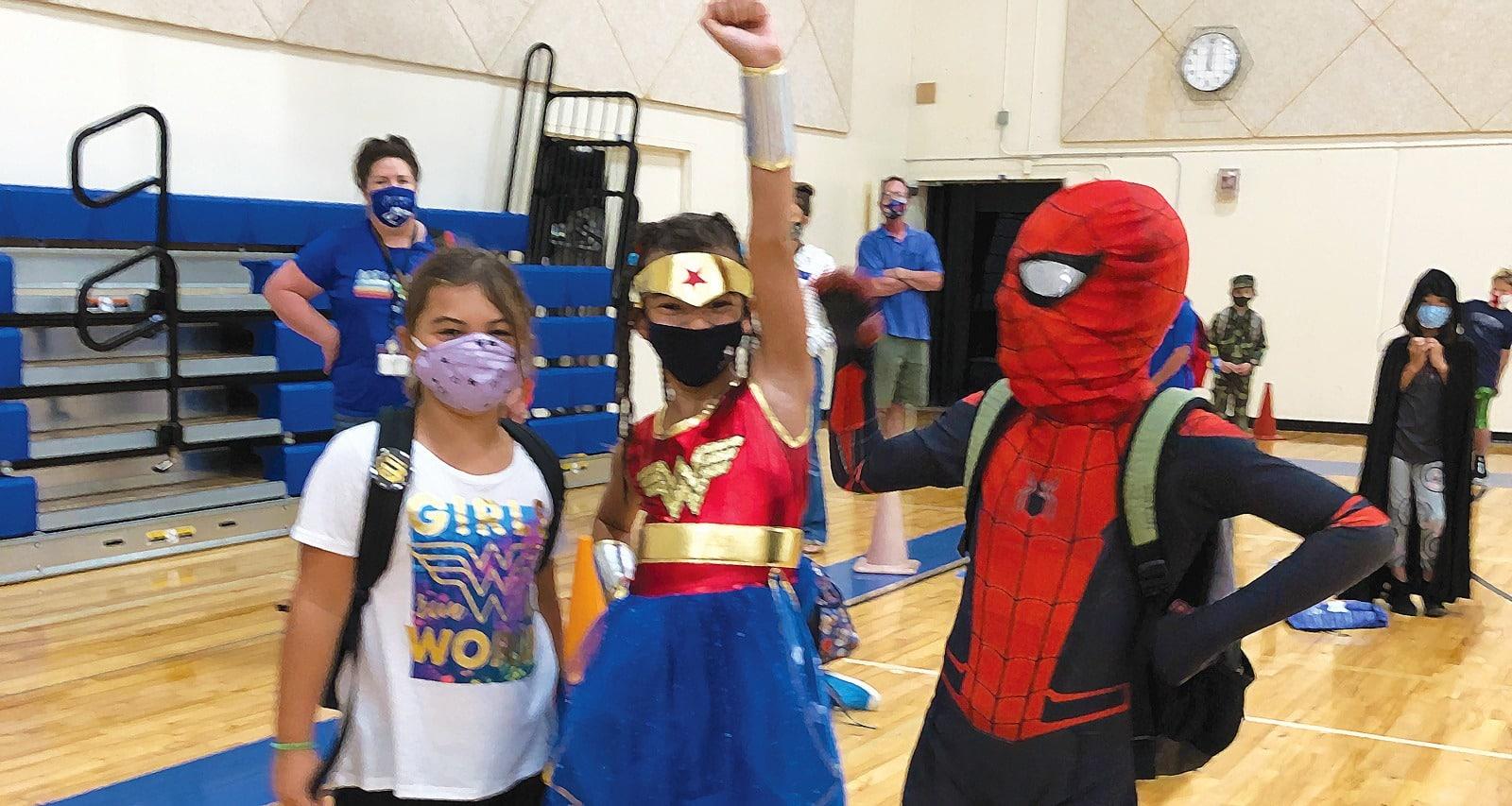 3 kids in costume wearing masks